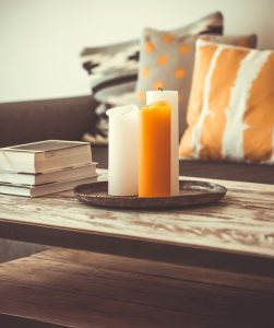white and orange candles sitting on a wooden coffeetable